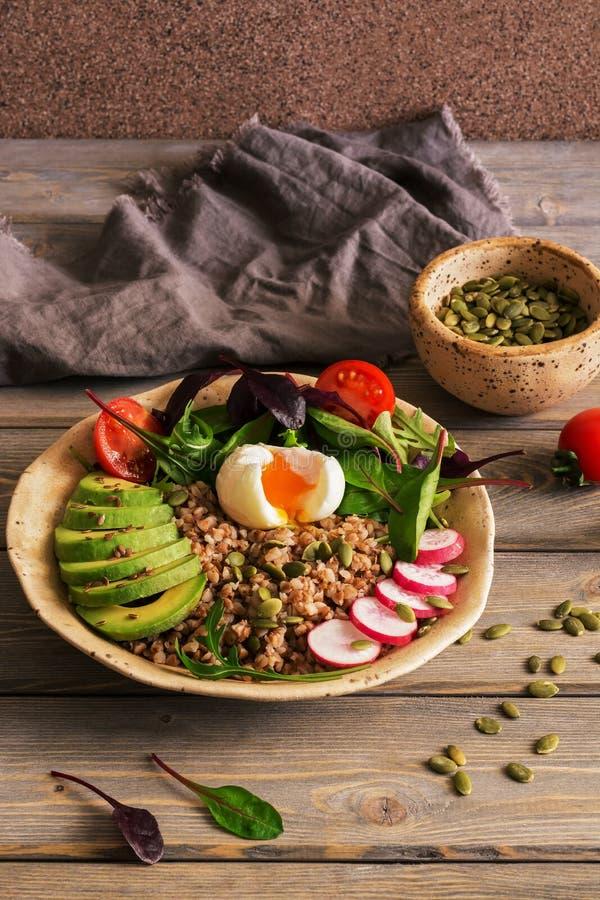 Bovetehavregröt med det kokta ägget, avokado, rädisa, chardsidor, frö på en träplankatabell BunkeBuddha Selektivt fokusera royaltyfria bilder