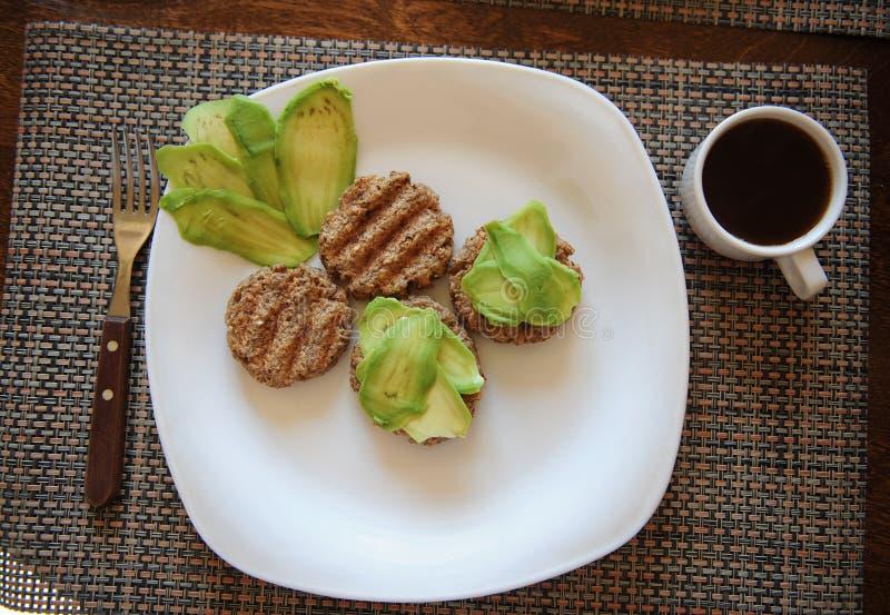 Bovetekotletter grillar och skivor av avokadot på den vita plattan Gaffel med trähandtaget Kupa av kaffe sund frukost royaltyfri fotografi