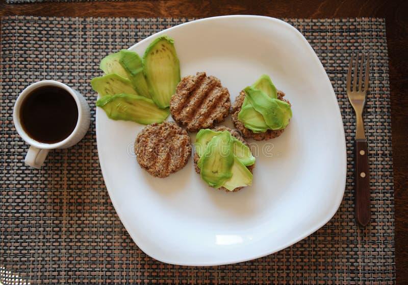 Bovetekotletter grillar och skivor av avokadot på den vita plattan Gaffel med trähandtaget Kupa av kaffe sund frukost royaltyfria bilder