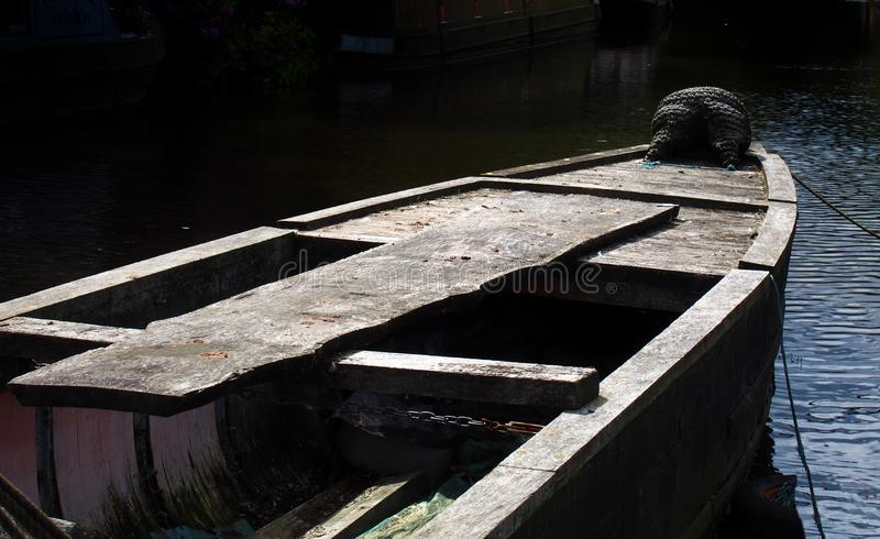 Bow of an ancient wooden boat in shadow in dark dark evening sunlight moored with ropes in blue water royalty free stock photography