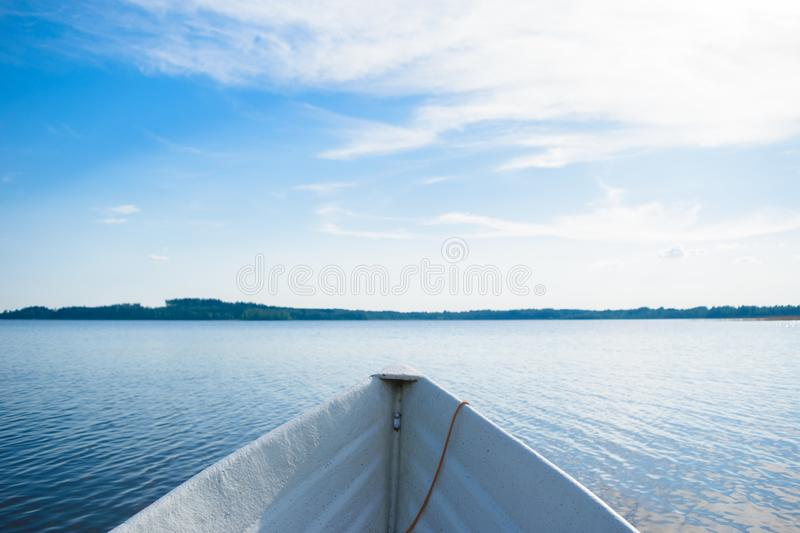 The bow of the boat on the lake. The bow of a white rowing boat on a smooth blue lake, looking at the horizon somewhere in the depths of Finland, a good summer royalty free stock image