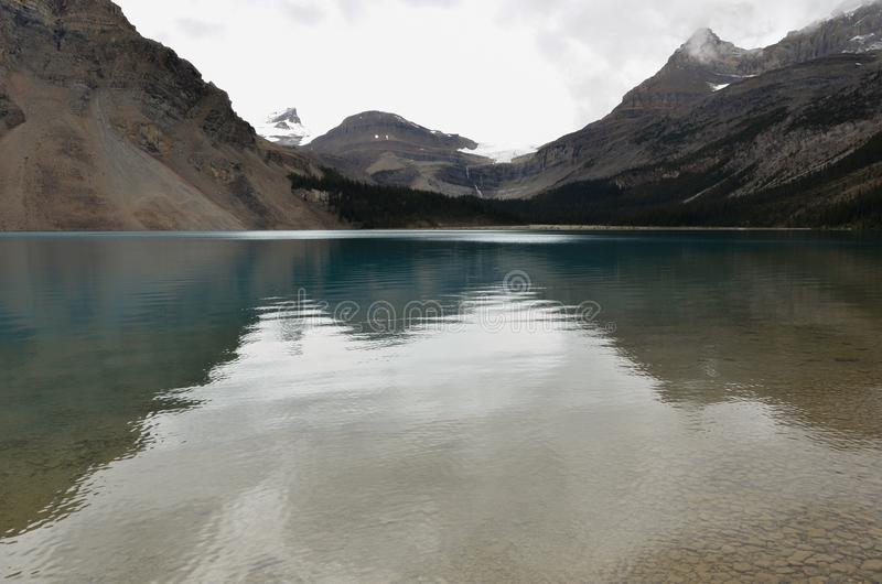 Bow Lake 6. Bow Lake, clear water surrounded by mountains on a cloudy day royalty free stock image