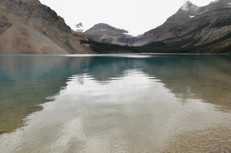 Bow Lake 5. Bow Lake, clear water surrounded by mountains on a cloudy day stock photography