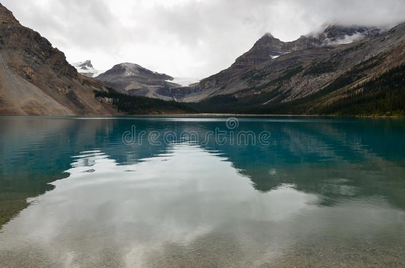 Bow Lake 3. Bow Lake, clear water surrounded by mountains on a cloudy day royalty free stock image