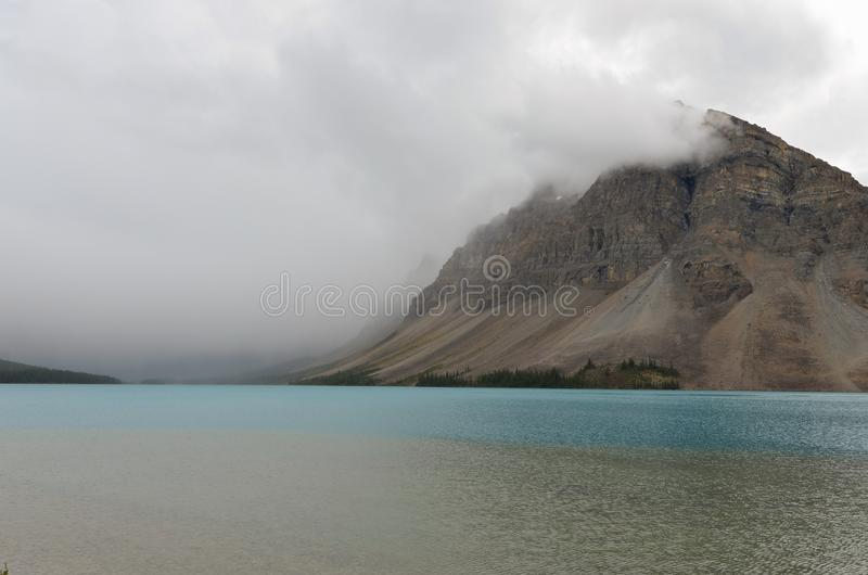 Bow Lake 9. Bow Lake, clear water surrounded by mountains on a cloudy day royalty free stock photography