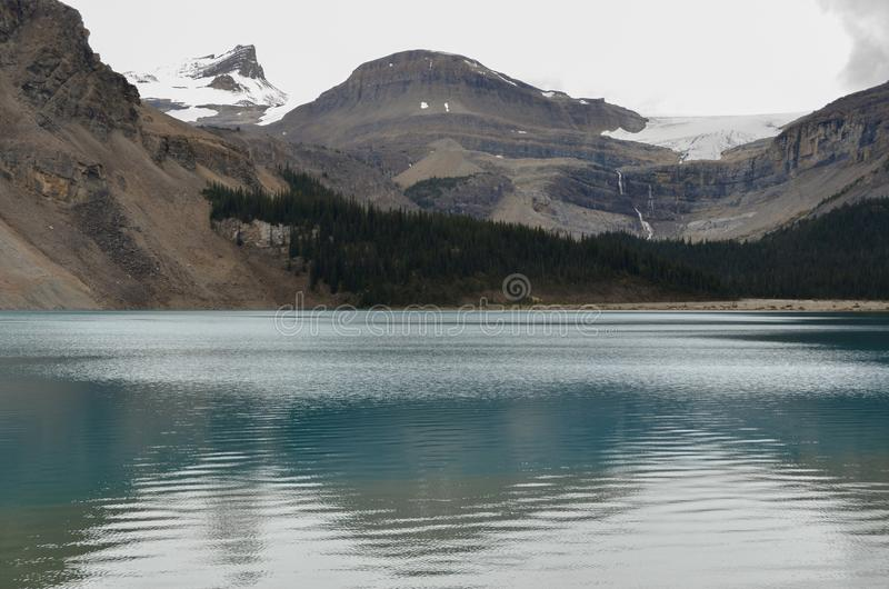 Bow Lake 7. Bow Lake, clear water surrounded by mountains on a cloudy day stock photos