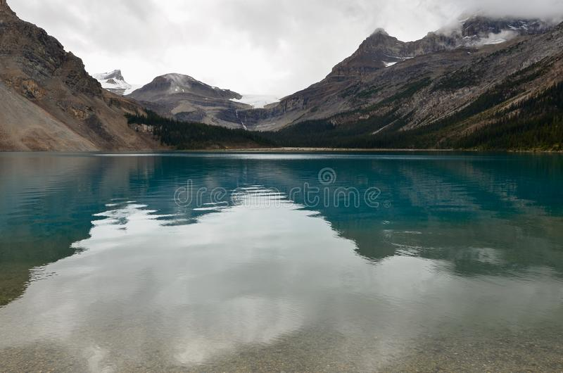 Bow Lake 2. Bow Lake, clear water surrounded by mountains on a cloudy day stock photo