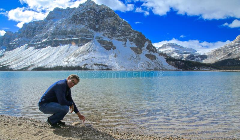 Bow Lake Man. Man feels freezing cold water in Bow Lake Canada after the snow royalty free stock image