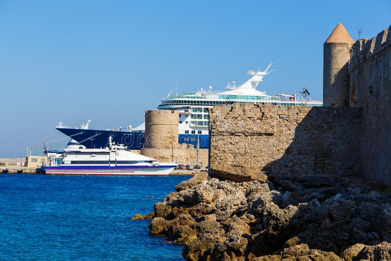 Bow of large cruise ship in the port of the ancient city, protruding from behind the fortress and tower of the ancient Fort. The. Bow of a large cruise ship in royalty free stock images