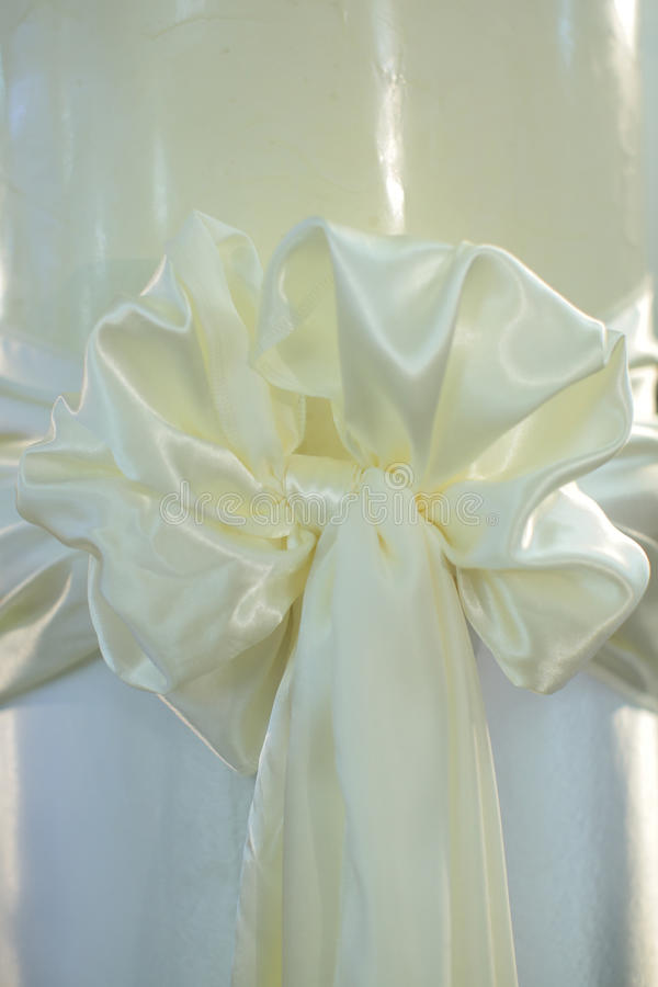 Bow made of white silk. Beautiful bow festive decorative ornamental knot with tail made of white silk ribbon on whiten background royalty free stock image