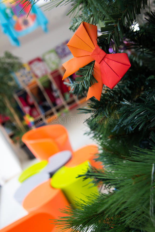 Bow Origami decoration in Christmas Tree. Orange Bow Origami decoration in Christmas Tree inside a school stock images