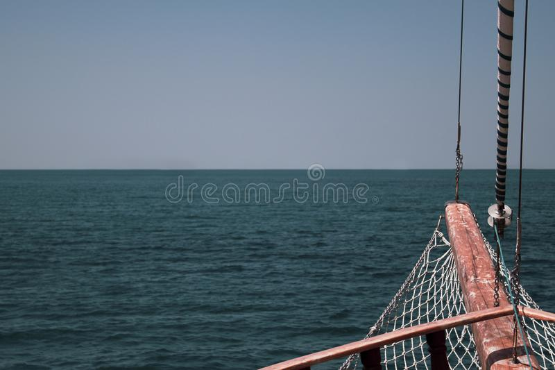 The bow of the ship against the sea horizon with a grid, steel cables and a folded sail. stock photo