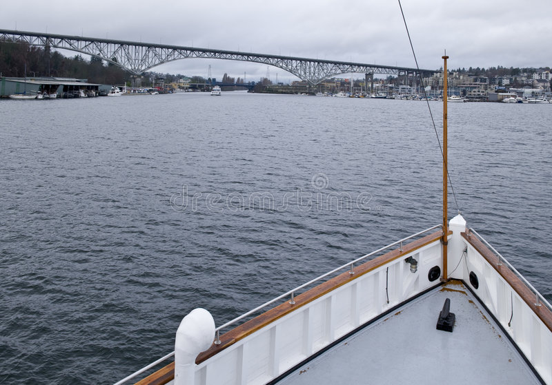 Bow of steamship on lake. A view of the bow and front deck of the historic steamboat, Virginia V, on Lake Union in Seattle, Washington with Highway 99 and bridge stock image