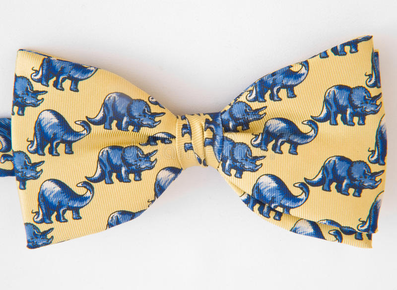 Bow tie. A bow tie in yellow with an elephant pattern is shown isolated on a white background royalty free stock photography