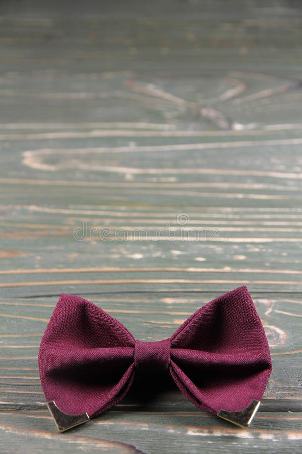 Bow tie coloring Marsala on a wooden background royalty free stock images