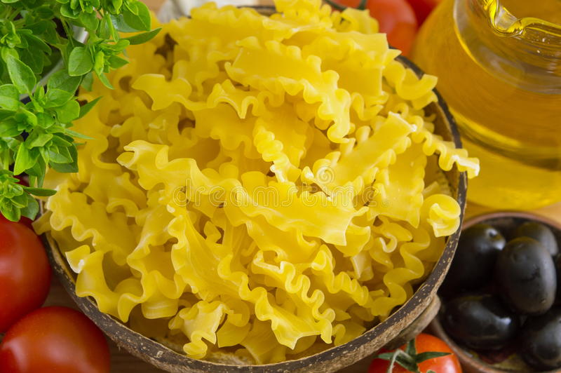 Bow tie farfalle pasta in a bowl with vegetables. On the table stock photos