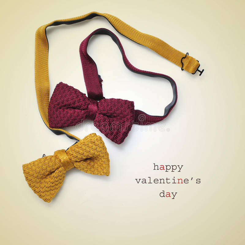 Bow ties and text happy valentines day. Two bow ties, one of them forming a heart, and the text happy valentines day written on a beige background royalty free stock photo