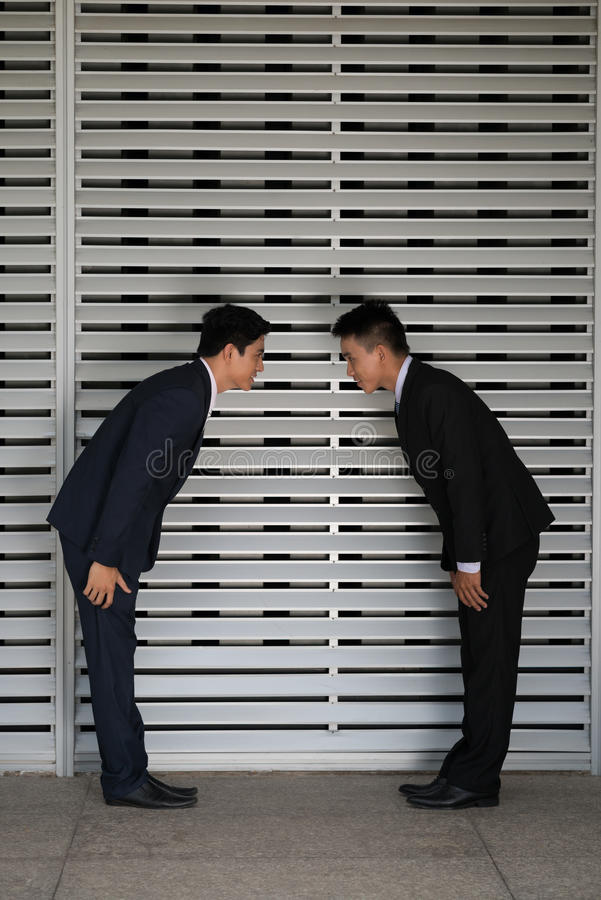 Bow. Two Asian businessmen bowing at office stock images