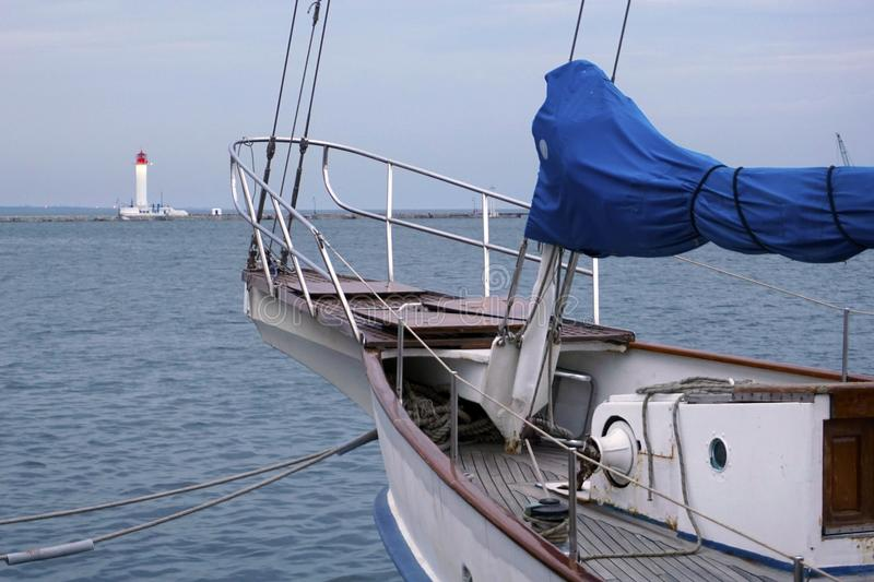 Bow of a white sailing yacht against the blue sea with anchor at the bow. lighthouse at the back side stock photography