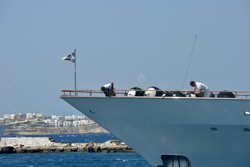 Bow of white yacht moored in the Mykonos harbor with two sailor man working royalty free stock image