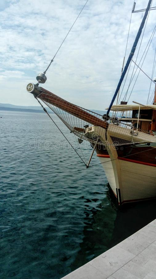 Bow of a wooden boat at sea. In the background a blue sky with small clouds stock photos