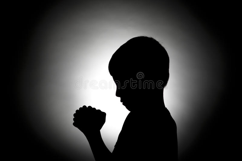 Bowed in prayer silhouette. The silhouette of a young boy bowed in prayer royalty free stock photos