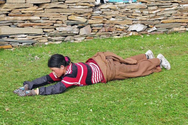 Bowed que ruega a la muchacha tibetana foto de archivo