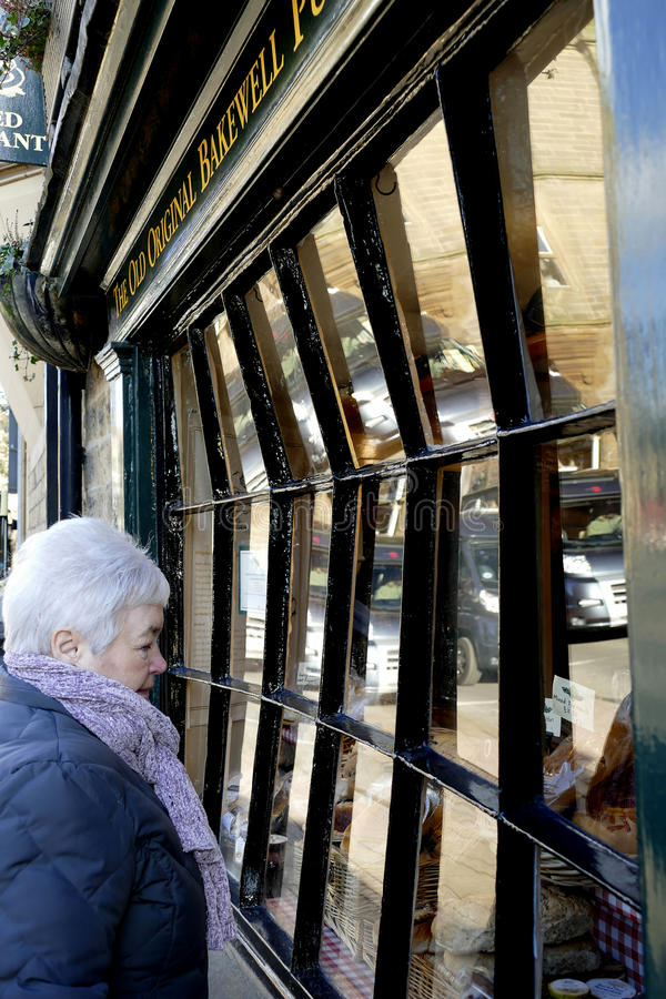 Bowed Window. BAKEWELL, DERBYSHIRE, UK. FEBRUARY 24, 2016. A senior lady browseing a shop with a bowed window at Bakewell in Derbyshire, UK stock photo