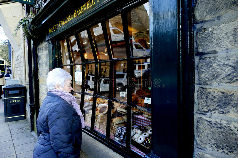 Bowed Window. BAKEWELL, DERBYSHIRE, UK. FEBRUARY 24, 2016. Senior lady looking in a bowed window at Bakewell in Derbyshire, UK stock photo