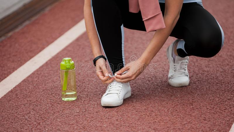 Bowed woman`s hands are tying sneakers on treadmill, getting ready for a run. Next to the foot is a green sports bottle. royalty free stock image