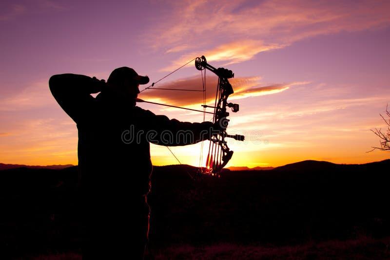 Bowhunter dans le coucher du soleil image stock