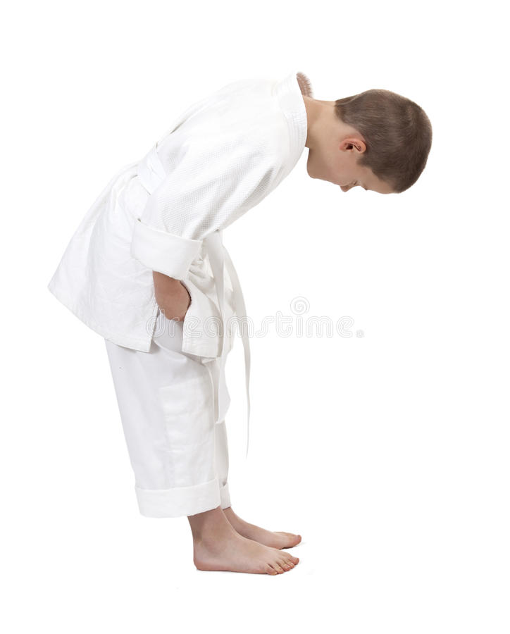 Bowing boy in judo kimono,. Isolated on white stock photography