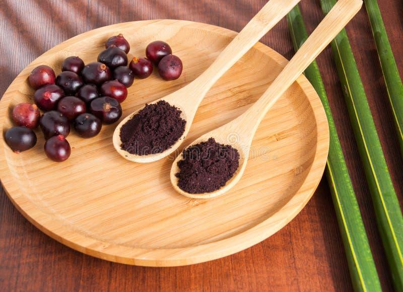 The amazon acai fruit. Euterpe oleracea. Bowl of acai powder and fresh berries on dark wooden table royalty free stock photography