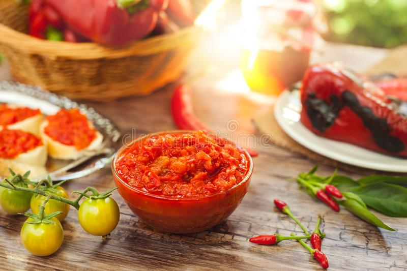 Bowl with ajvar on the table. Bowl with ajvar on wooden table with chili peppers royalty free stock image