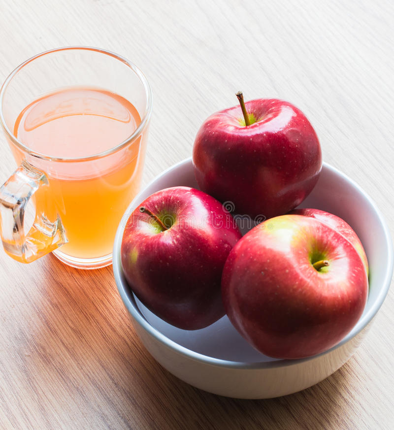 Bowl of apples and glass of juice. stock image