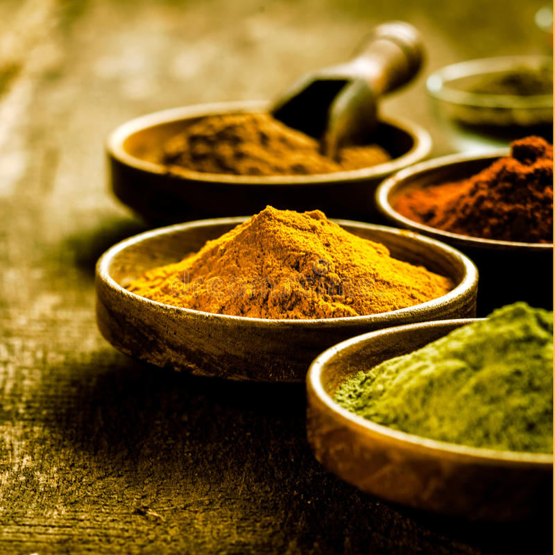 Bowl of Asian curry powder. Blended from a mixture of spices with turmeric and masala, selective focus on a grunge rustic wooden surface stock photo