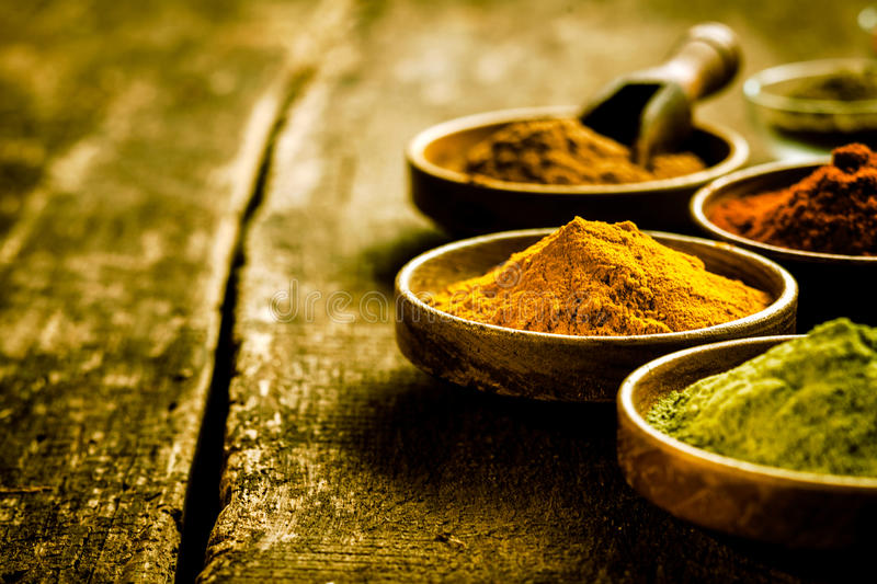Bowl of Asian curry powder. Selective focus to a bowl of Asian curry powder on old wooden boards amongst an array of other ground spices, with copyspace stock image