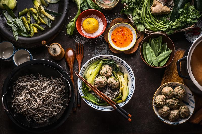 Bowl with asian meatballs noodle soup and chopsticks on dark rustic kitchen table with green vegetables ingredients. To view. Asian cuisine. Asian food dishes stock photos
