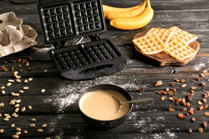 Bowl with batter, maker machine and fresh waffles on dark wooden table stock image