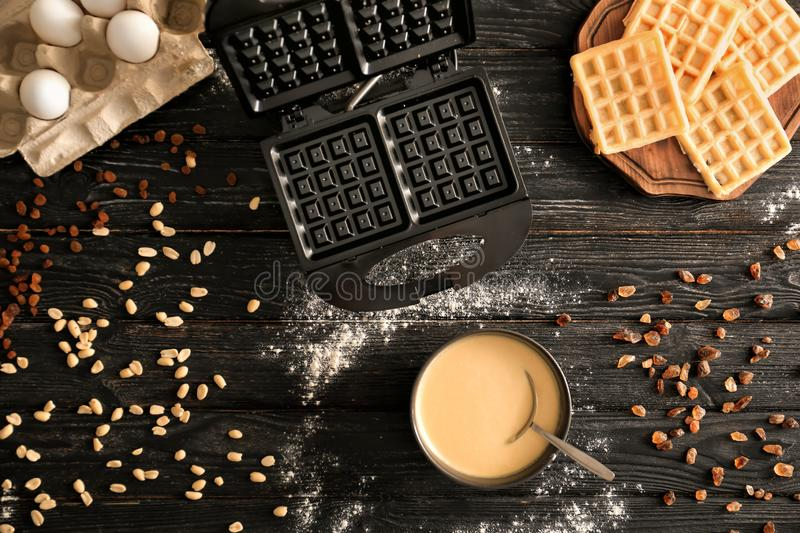 Bowl with batter, maker machine and fresh waffles on dark wooden table royalty free stock photography