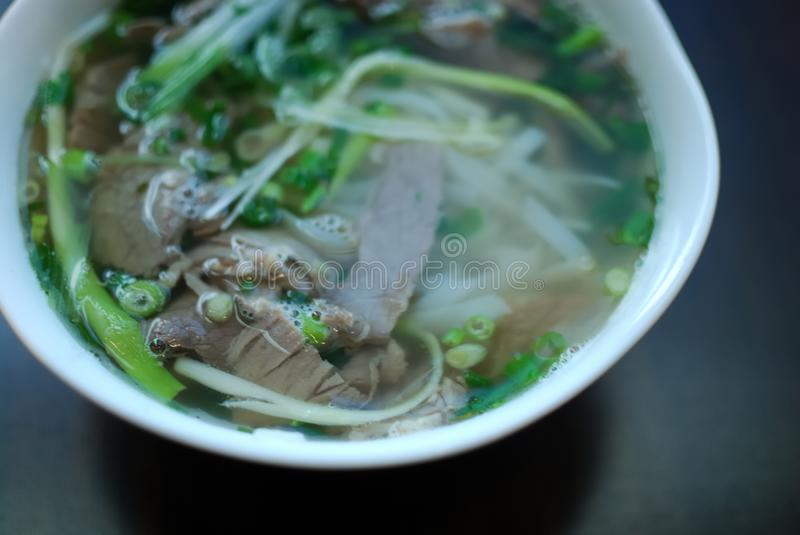Bowl of beef pho close up look. Vietnamese traditional rice noodle soup with beef. royalty free stock photography