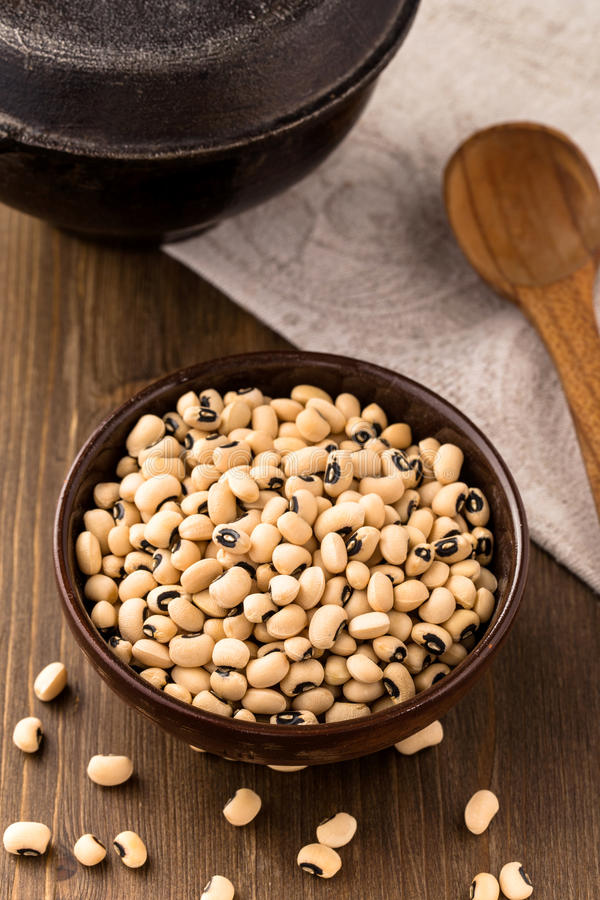 Bowl of black-eyed bean above. Bowl of black-eyed beans on wooden background above stock photos