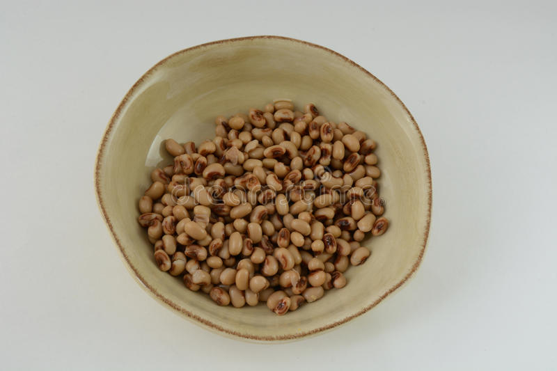 Bowl of black eyed peas. Black eyed peas in brown bowl, a food traditionally eaten in the Southern United States on New Year's Day to bring good luck for the stock photos