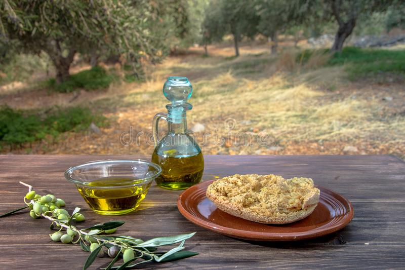 Bowl and bottle with extra virgin olive oil, olives, a fresh branch of olive tree and cretan rusk dakos on wooden table. stock photography
