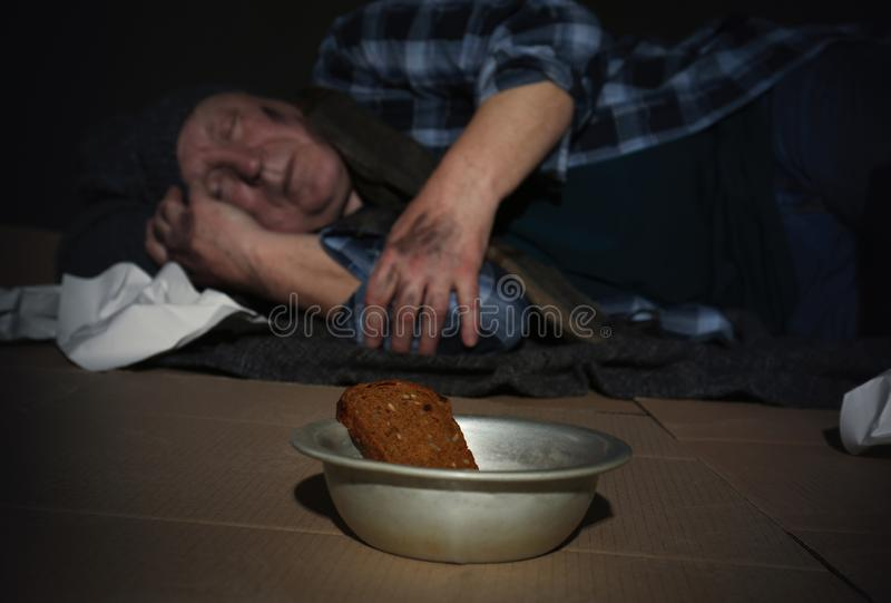 Bowl with bread and poor senior on floor royalty free stock photography