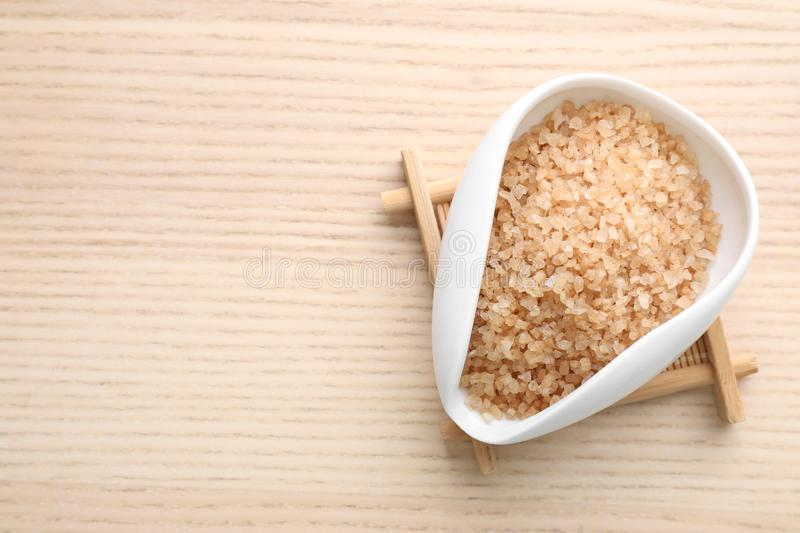 Bowl of brown sea salt on wooden table, space for text. Spa treatment. Bowl of brown sea salt on wooden table, top view with space for text. Spa treatment stock photo