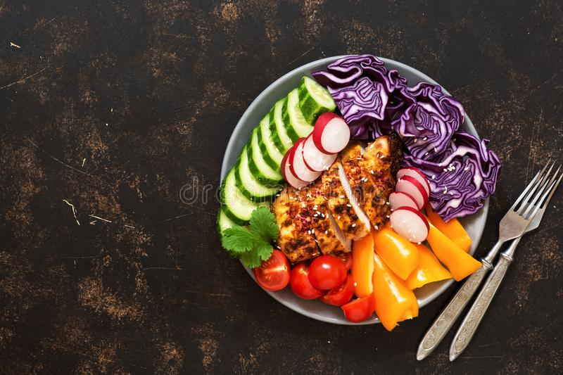 Bowl of buddha with baked chicken fillet and fresh vegetables on a dark background, top view. Copy space. stock photos