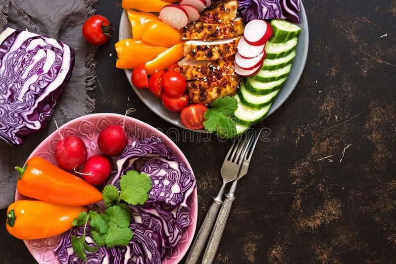 Bowl of buddha with baked chicken fillet and fresh vegetables on a dark background, top view. Copy space stock images