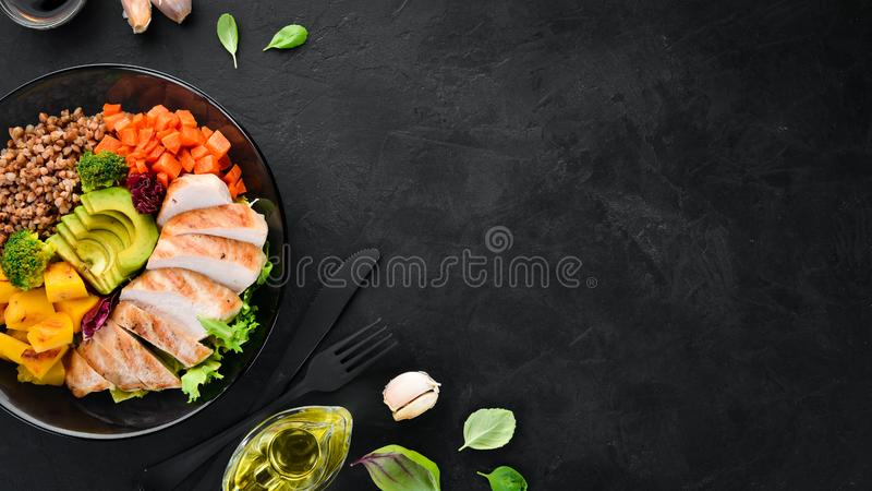 Bowl Buddha. Buckwheat, pumpkin, chicken fillet, avocado, carrots. On a black background. royalty free stock photos