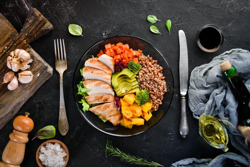 Bowl Buddha. Buckwheat, pumpkin, chicken fillet, avocado, carrots. On a black background. royalty free stock photo